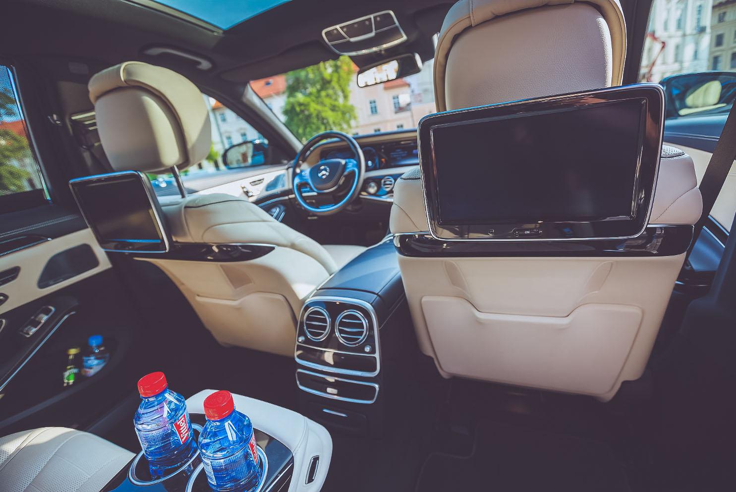 Pohled do Mercedes-Benz S-Class, kde je vidět výbava auta k pronájmu s řidičem. Dvě pitné vody v opěrátku, tv na zadních sedačkách. Bílá kůže a celkový luxusní vzhled
